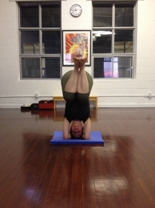 Lifting up into Sirsasana with bent knees.